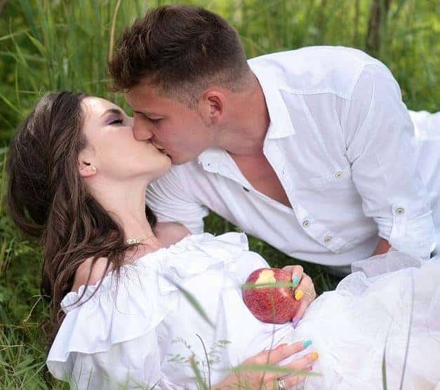 man and woman in white clothes intimate